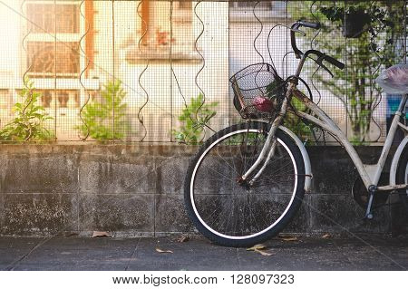 Old bicycle leaning against grunge concrete wall
