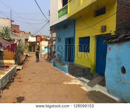 India, Khajuraho, - February 27, 2015: Old town street and a boy in indian village, blue and yellow houses, street life in India