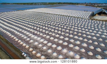 aerial view Heap of sea salt in original salt produce farm make from natural ocean salty water preparing for last process before sent it to industry consumer