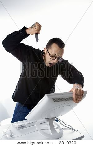 Caucasian mid-adult man with tattoos and piercings stabbing computer with knife.