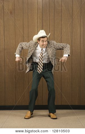 Mid-adult Caucasian male wearing cowboy hat dancing.
