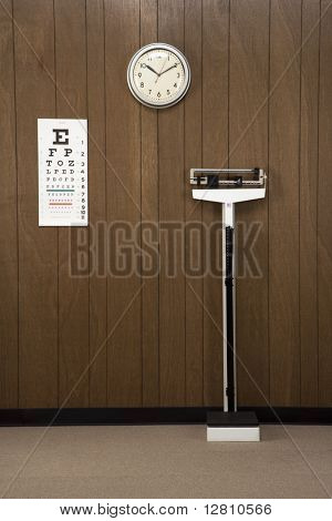 Retro doctor's office with wood paneling, clock, eye chart and scale.