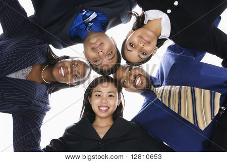 Low angle portrait  of multi-ethnic business group of men and women in huddle looking at viewer.