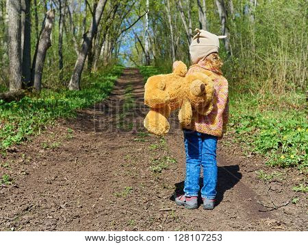 Child Is Walking Down  Path With  Teddy Bear