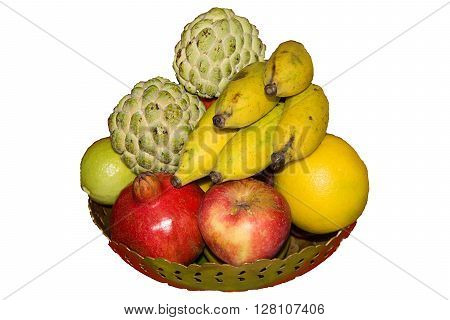 Fruit bowl of brass containing apple pomegranate sweet lemon lemon bananas and custard apples isolated on white