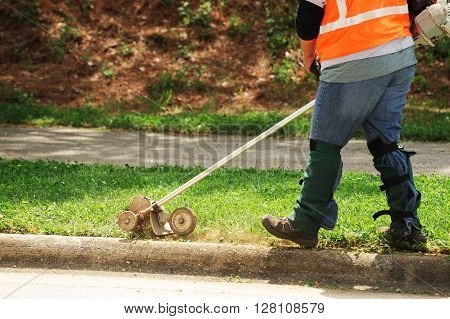 outdoor worker working on trimming the lawn at sidewalk