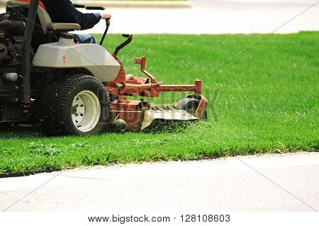outdoor worker mowing the lawn with driving lawn mower