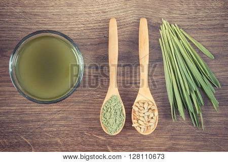 Vintage photo Barley grass with cup of beverage and grain with young powder barley on wooden spoon healthy nutrition and lifestyle body detox
