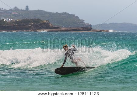 Manly Australia - November 9 2014: A Australian surfer on the wave. Seven miles from the heart of Sydney famous Manly beach offers a wide range of sports and recreational activities.