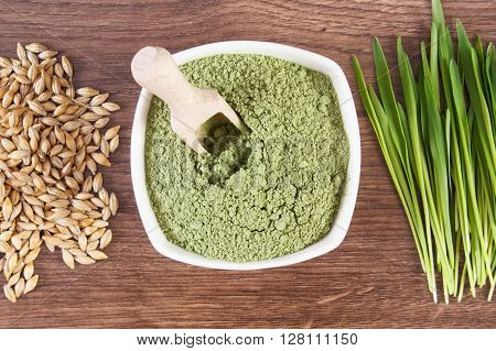 Heap of young powder barley in dish barley grass and grain on wooden background healthy nutrition and lifestyle body detox
