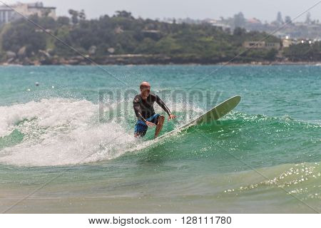 Manly Australia - November 9 2014: A man surfing a wave in Manly beach tries to keep balance. Seven miles from the heart of Sydney famous Manly beach offers a wide range of sports and recreational activities.