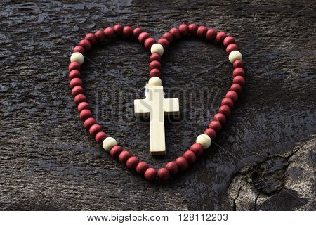 the rosary arranged in a heart shape on the old board