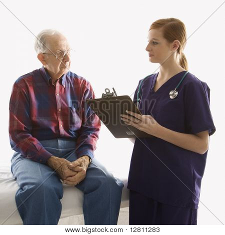 Mid-adult Caucasian female in scrubs taking notes from elderly Caucasian male.