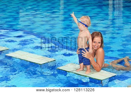 Little happy sports man in underwater goggles - active baby swim with fun jump to mother hands in swimming pool. Family lifestyle and summer children water activity and swimming lesson with parents.