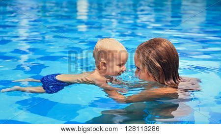 Happy little sports man has swimming lesson with mother - active baby swim with fun in woman hands in swimming pool. Family lifestyle and summer children water activity and swimming lesson with parent