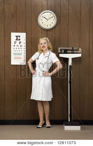 Caucasian mid-adult female nurse with hands on hips smiling at viewer in retro doctor's office.
