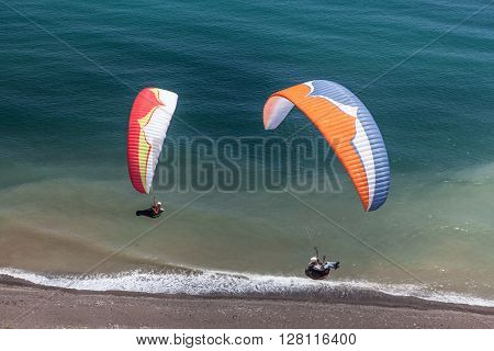 Two paragliders  are fluing above the sea