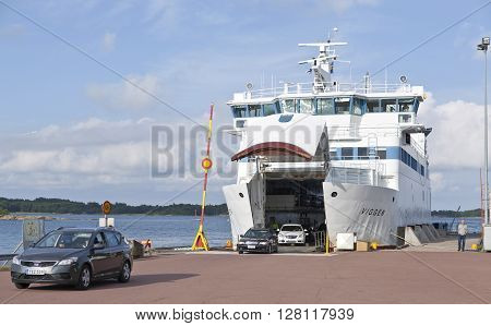 BALTIC SEA, ALAND ON JUNE 28. View of the white ferry Viggen arrives the harbor. Unload cars on June 28, 2013 in Ava, Aland. Unidentified people around. Editorial use.