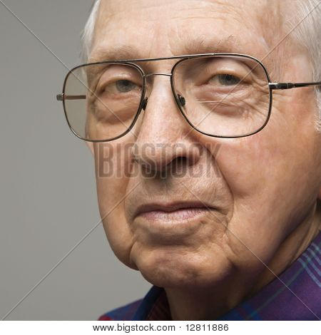 Close-up portrait of elderly man in glasses.