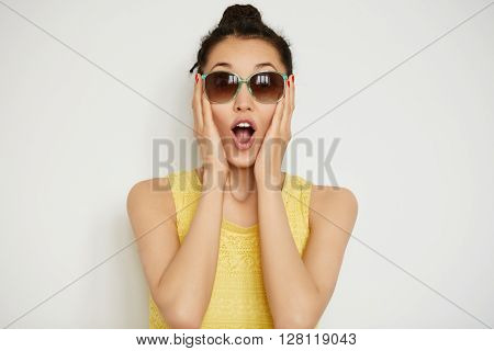 Happy Young Woman In Sunglasses Looking Surprised At The Camera, Holding Her Head In Excitement. Clo