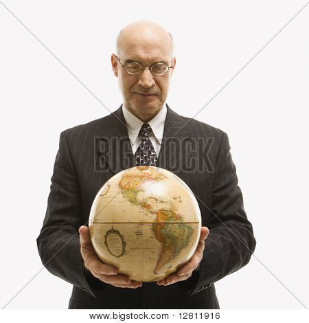 Caucasian middle-aged businessman holding globe in both hands standing in front of white background.