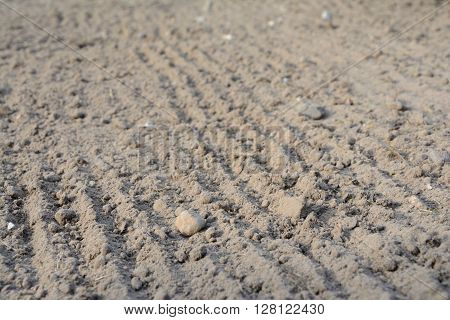 Photo of loosened soil with blurred foreground and background. Shallow depth of field.