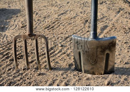 Pitchfork and spade stuck in the ground closeup.