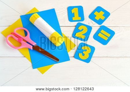 Paper cards with numbers, scissors, paper sheets, glue on a white background. Education concept