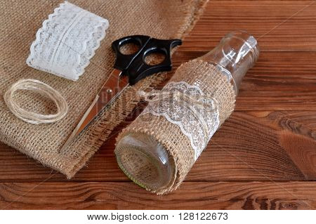 Homemade diy glass bottle. Scissors, burlap, handmade vase on a wooden table. Rustic style. DIY concept.