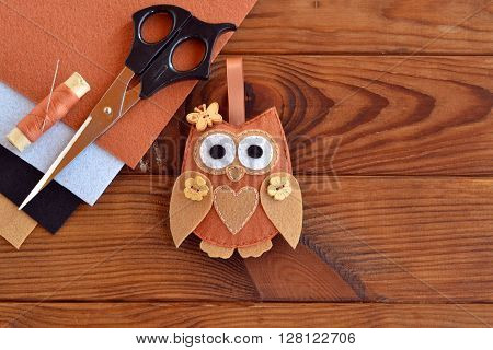 Felt brown owl. Shabby chic style. Kids crafts. Scissors, thread, needles, felt sheets - sewing kit. Brown wooden table