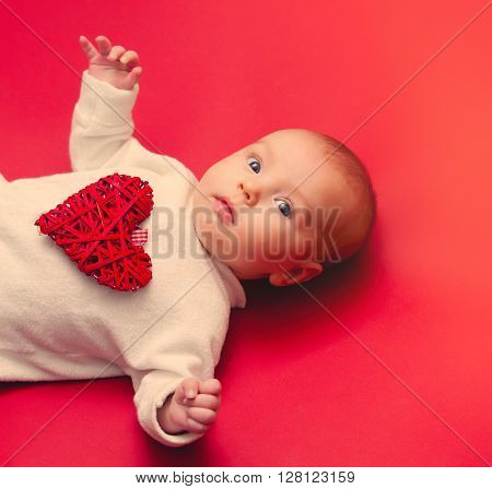 little baby lying down on red backgorund with heart shape toy as a gift for Valetine's Day