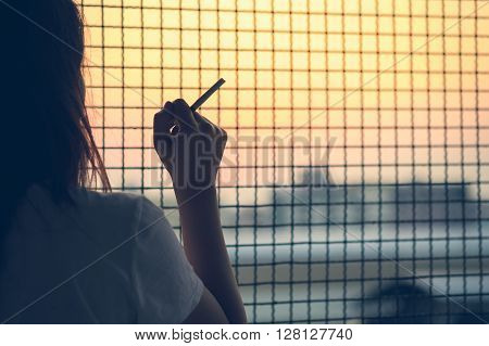 Woman holding a cigarette in the fence, social issue, smoker concept.