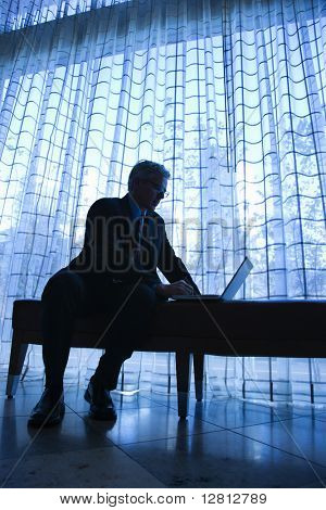 Blue tone silhouetted image of prime adult Caucasian man in suit sitting on bench typing on laptop.