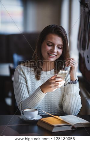 smiling woman using her smartphone phone at cafe ** Note: Visible grain at 100%, best at smaller sizes