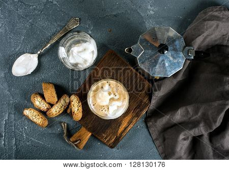 Glasses of coffee with ice cream on rustic wooden board, steel Italian Moka pot over grey concrete textured background, top view, horizontal