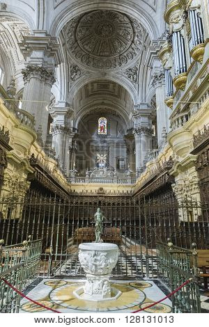 Jaen, Spain - may 2 2016: View of the entrance to the choir, one of the largest in Spain, stack baustismal of white marble of Carrara with a statue of Jesus risen made in bronze, completed in the 18th century, Spain
