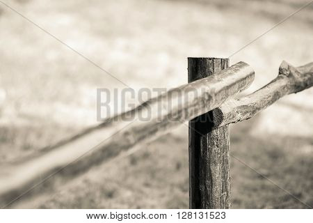 part of an old column and poles from a wooden fence for the ranch closeup on an indistinct background of beige color
