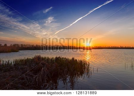 Sunset over a swamp lake aircraft trail in the sky.