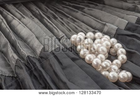 Pearl necklace on black and grey creased satin background