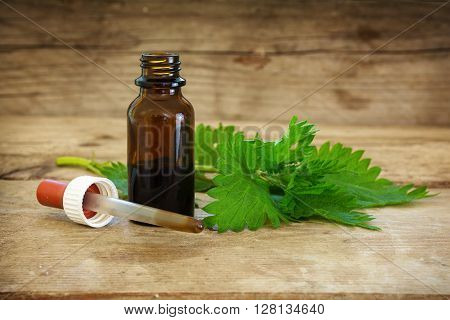 nettle tincture in a small bottle and fresh leaves on a rustic wooden background medicinal herb for overweight diabetis and kidney weakness selected focus narrow depth of field