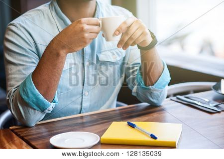Close up of male hands holding a cup of coffee. He is sitting at desk in cafe
