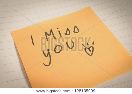 Handwritten I miss you word and heart shape on sticky note in opened notebook. Colored filter effect.