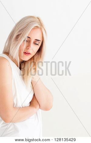 Woman with pain in neck on white background. Massage therapy of painful neck. Tired neck after long working hours. Woman relaxes the neck.