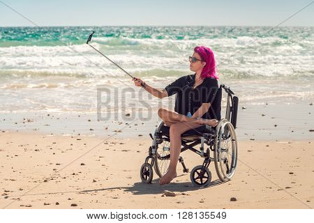 Disabled woman in the wheelchair at the beach taking selfie photos with her mobile phone on selfie stick