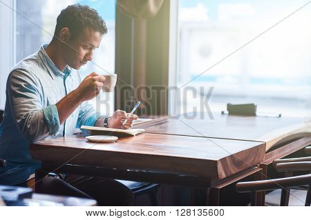 Attractive young eastern guy is sitting at table in cafe. He is making notes into writing-pad with seriousness. The guy is drinking hot coffee