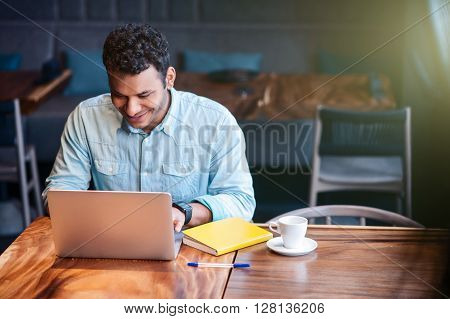 Attractive man is working on the laptop in cafe. He is looking at monitor with joy and smiling. The man is sitting at table in cafeteria