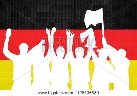 Silhouette of cheering soccer fans in front of wall with german colors