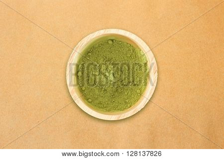 Wooden bowl of green tea powder on brown paper background, stock photo