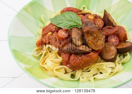 Chorizo sausage and tomato pasta meal with basil in plate isolated on white table