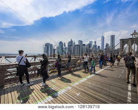 NEW YORK CITY - April 22: The pedestrian walkway along The Brooklyn Bridge and taking photos in New York City on April 22, 2016, New York, USA